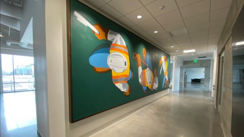 The colorful  26' At Work canvas mural is meant to capture an energetic and harmonious work ethic that makes impressive feats of construction possible and turns clients' dreams into reality.