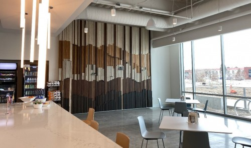 The floor-to-ceiling Skyline Café Focal Wall piece was created especially for Jacobsen from reclaimed wood sourced from the company's own materials yard. This multi-dimensional piece is layered to represent the depth of Jacobsen's important work and rises tall as a testament to the company's bright future. The city horizon line found within the piece symbolizes the elevating skyward reach of the gleaming cities and the thriving communities Jacobsen builds.